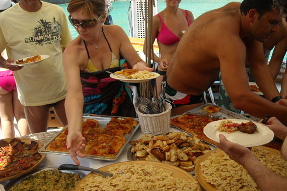 Visitors eating traditional Greek food while sailing